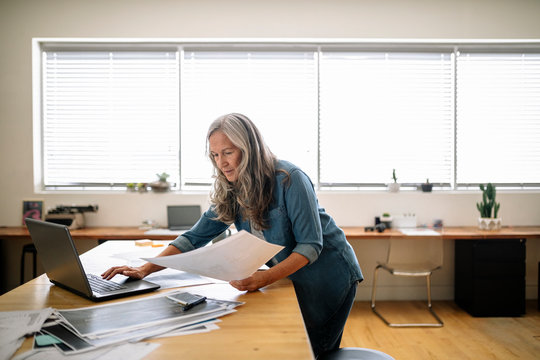 Creative female designer reviewing proofs in office