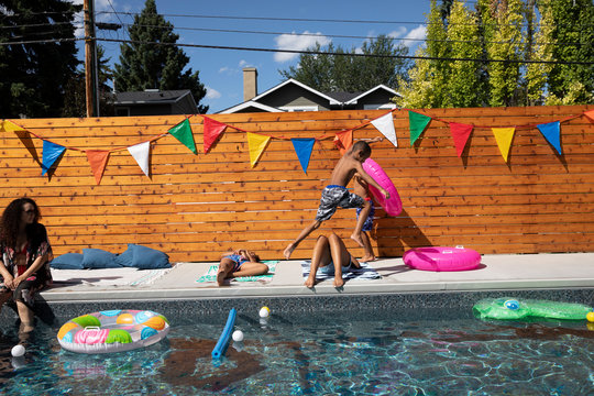 Playful boy jumping over sisters at sunny, summer poolside