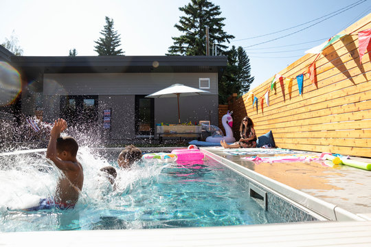 Brothers and sister jumping into summer, sunny swimming pool
