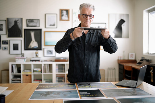 Creative senior male designer photographing proofs with digital tablet in office