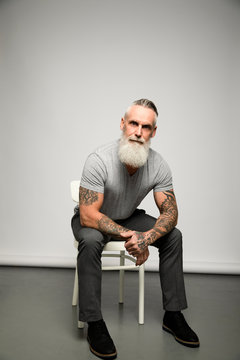 Portrait confident, strong man with gray beard and tattooed arms