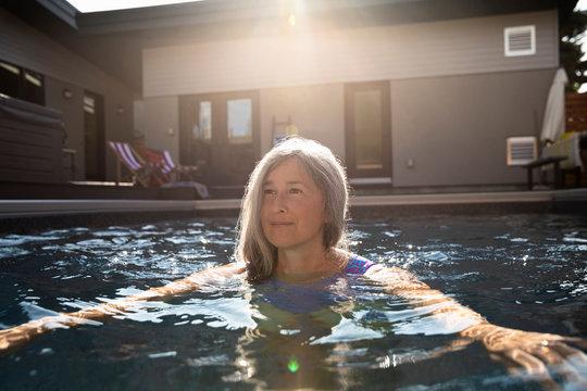 Serene senior woman swimming in sunny, summer swimming pool