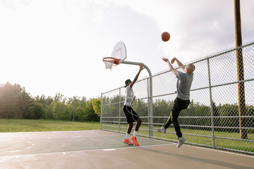 Basketball player aiming to score goal with opponent jumping to defend