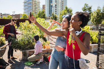 Playful young women friends with carrots taking selfie with camera phone in sunny, urban community garden