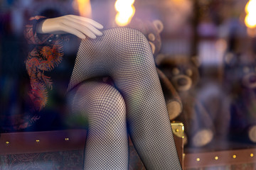 legs of a mannequin girl in stockings in a shop window close-up