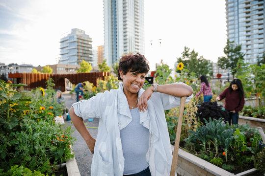 Portrait happy, carefree mature woman gardening in urban community garden