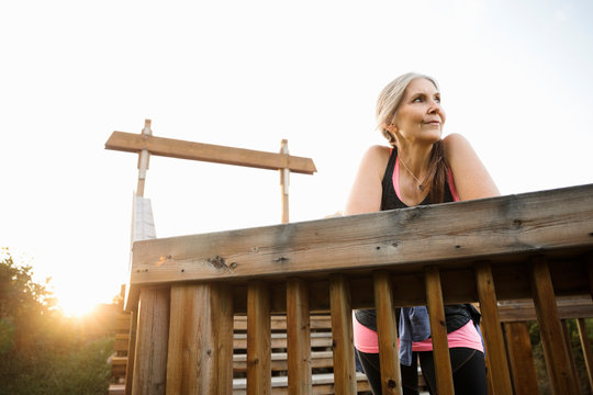 Portrait of mature women in sports clothing leaning on wooden fence