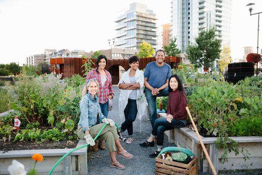 Portrait happy mature friends in urban community garden