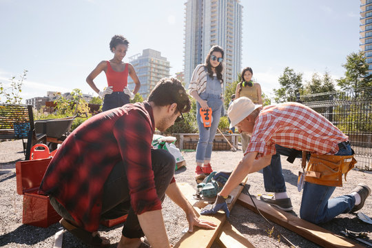 Man guiding young adults building planter box in sunny community garden