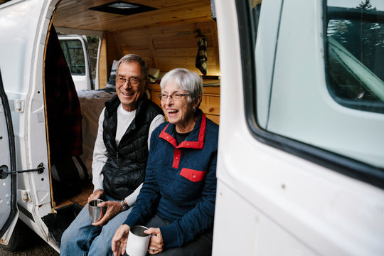 Happy senior couple relaxing, drinking coffee at camper van