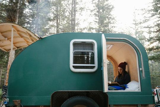 Woman relaxing, reading book in camper van