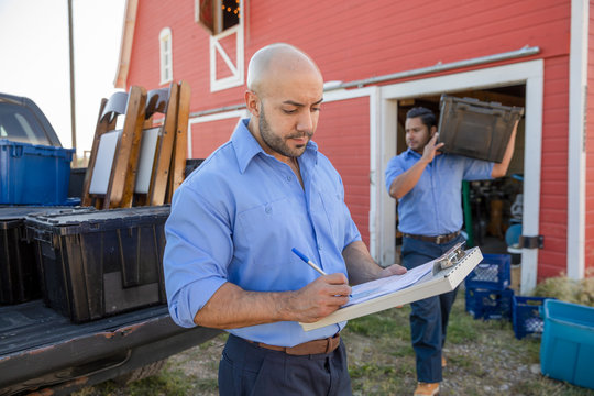 Event delivery man with clipboard outside barn