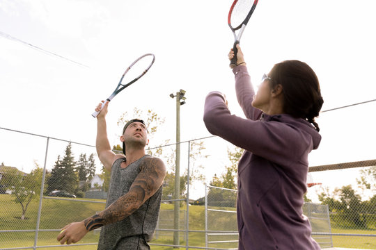 Man and woman practicing tennis serve