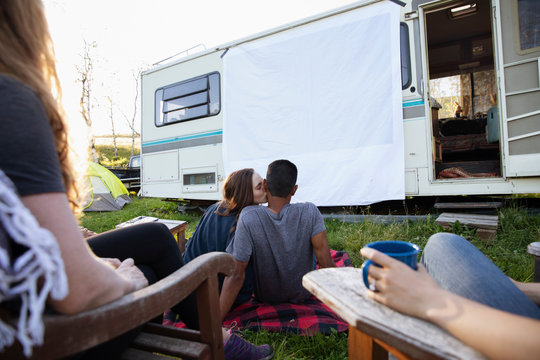 Young couple sitting outside motorhome watching movie