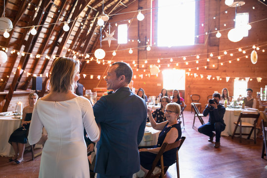 Mature bride and groom giving speeches at wedding reception in barn