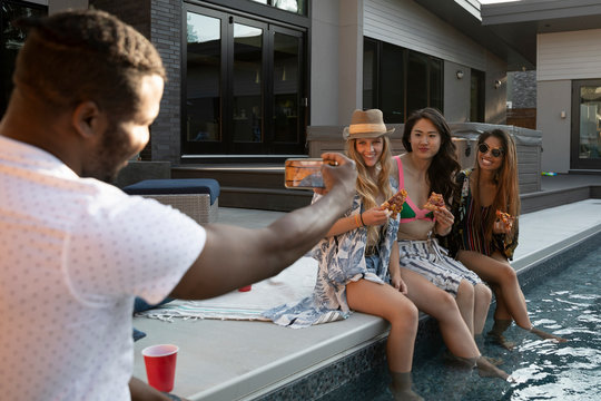 Man with camera phone photographing young women eating pizza at summer swimming pool