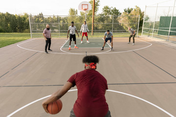 Basketball player with ball on basketball court with opponents