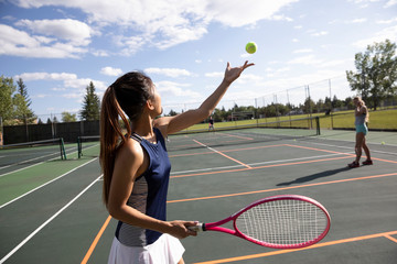 Young woman serving the ball, playing couples tennis on sunny tennis court