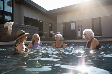 Happy senior women friends swimming, talking in sunny, summer swimming pool