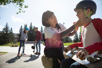 Mother fastening skateboard helmet on son in sunny skate park