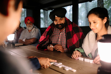 Indian family playing dominoes in log cabin