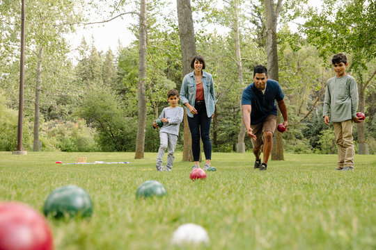 Family playing bocce in urban park