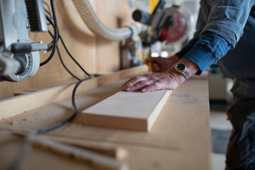 Carpenter leaning on plank of wood in workshop