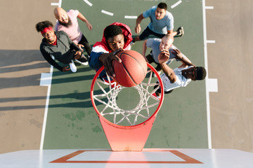 Overhead view of basketball player slam dunking ball in net