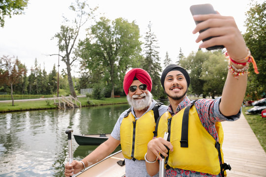 Mature Indian man and son wearing life jackets taking selfie