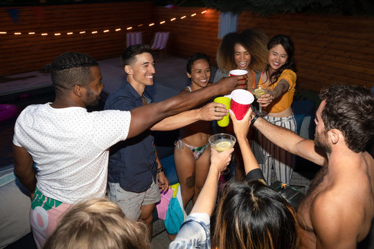 Young adult friends toasting cocktails on summer poolside patio at night