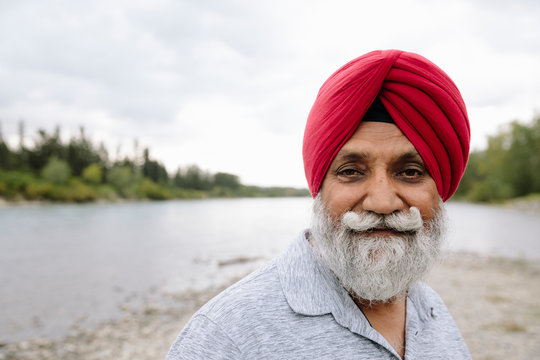 Portrait of Indian man wearing red turban on lake shore