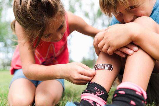 Girl helping her brother with sticking plaster on leg