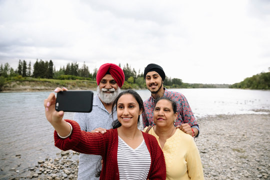 Indian family taking selfie on lake shore