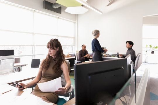 Businesswoman using phone at desk in modern office