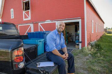 Portrait smiling event delivery man sitting at truck bed outside barn
