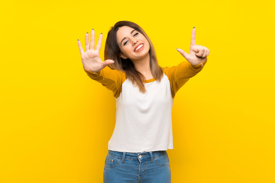 Pretty young woman over isolated yellow wall counting seven with fingers