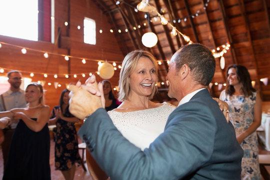 Happy mature bride and groom dancing at wedding ceremony