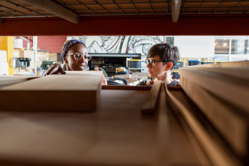 Two women looking at wood in storage in community workshop