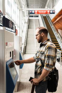 Man buying train ticket at machine in railway station
