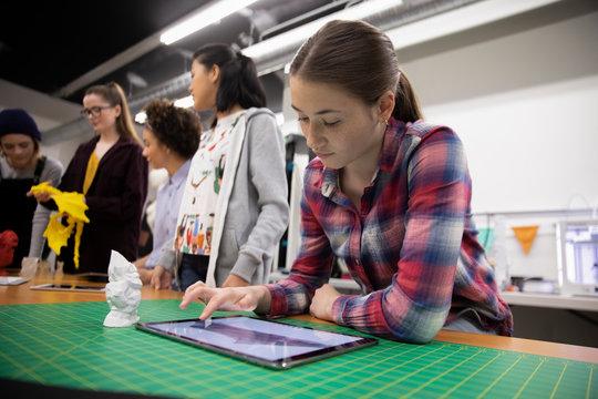 Student using digital tablet in 3d printing workshop