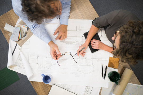 Overhead view of two colleagues discussing architectural plans