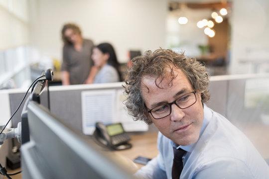 Businessman wearing glasses looking over shoulder