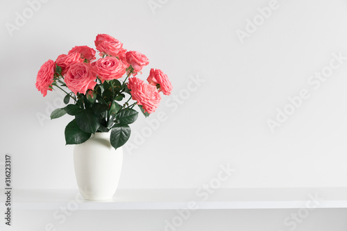 Beautiful flowers, pink roses. Roses in vase on shelf against white wall. Valentines Day, Easter, Happy Women's Day, Mother's day. Space for text.