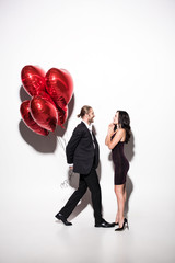 cheerful couple holding red heart shaped balloons on valentines day on white
