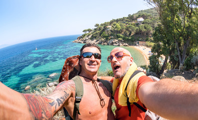 Best friends taking selfie at Giglio Island on adventure travel - Wanderlust lifestyle concept with gay couple enjoying happy fun moment - Trip together around world beauties - Bright vivid filter