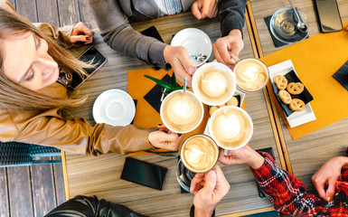 Top view of friends toasting cappuccino at coffee shop restaurant - Millennial students group...