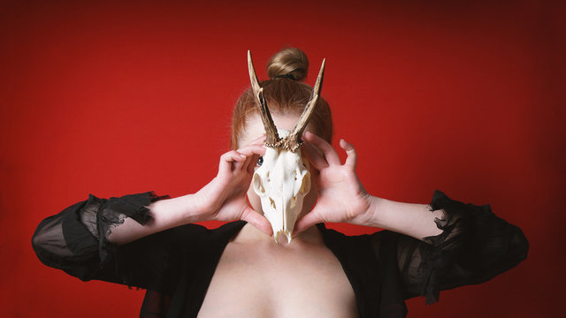 mysterious occult woman holding animal deer skull in front of her face - animalism witch or sorceress