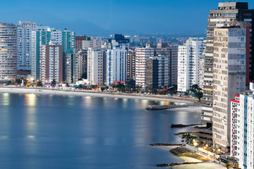 Urbanized coast, tall buildings near to the beach of a coastal city at dusk, when city lights begin to turn on. Paulista coast, Sao Vicente city - SP Brazil.
