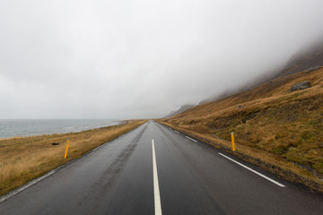 einsame Straße am Meer bei Regen und Nebel