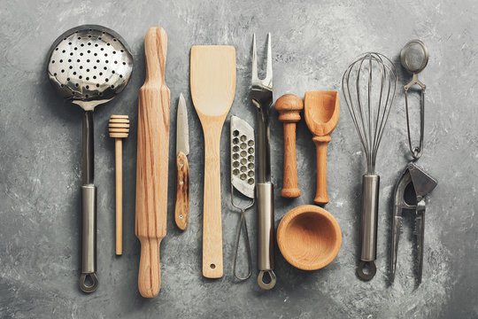 Flat lay kitchen tools and utensils on a gray concrete background, toned. Top view. Kitchenware is metal and wood.